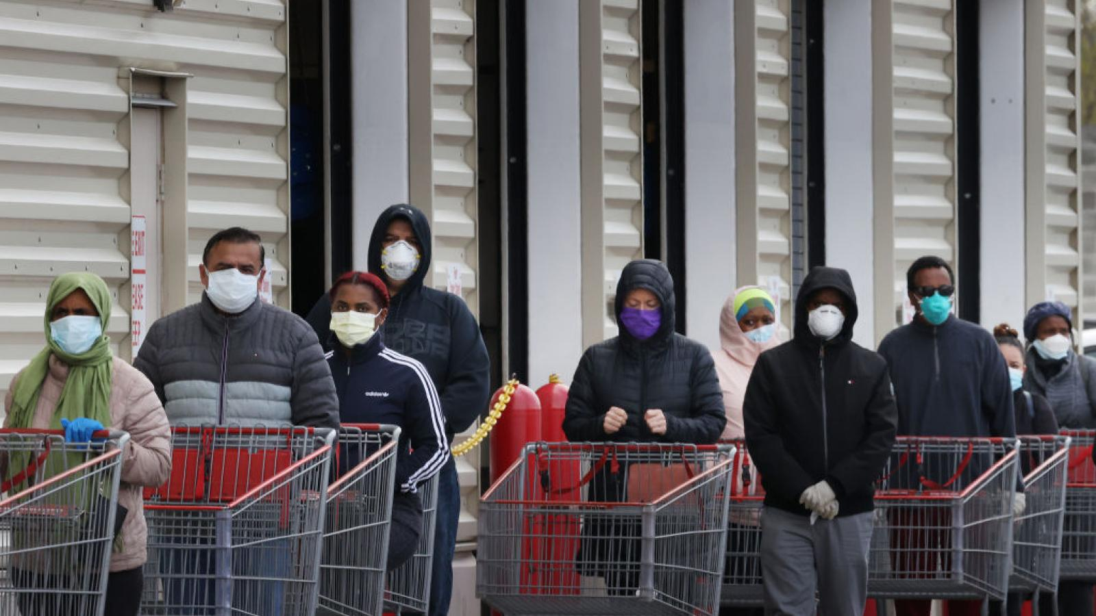 Shoppers wait in line while wearing masks