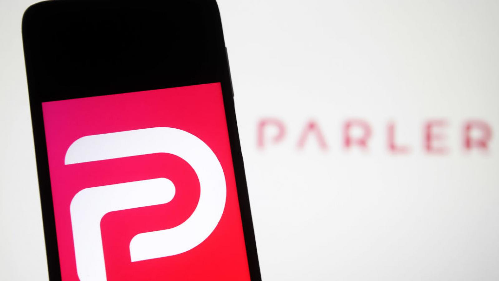 Parler logo displayed on phone in photo illustration